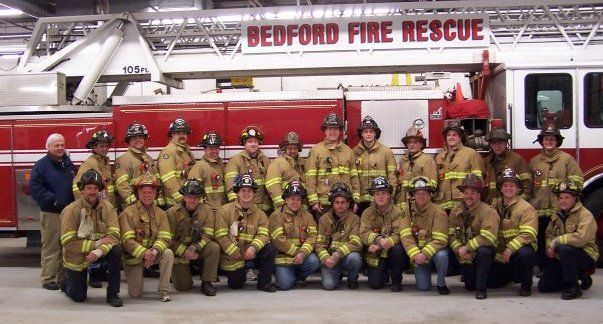 The Bedford Fire Rescue crew poses in uniform in front of a fire truck