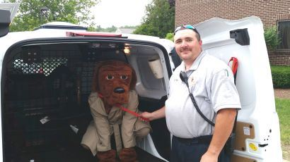 A man in a McGruff suit sits in the back of an animal control vehicle next to an officer